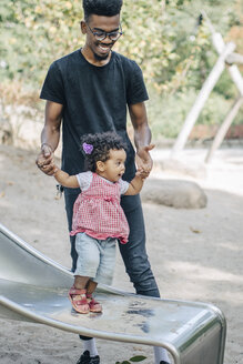 Young man holding hands of daughter standing on slide at playground - MASF10784