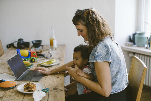 Woman using feeding food to daughter while sitting at dining table in house - MASF10799