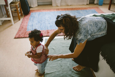 Mother adjusting clothes of daughter standing at home - MASF10802