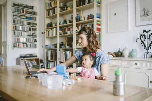 Woman using laptop while sitting with daughter at dining table in house - MASF10829