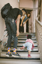 Father and mother looking at baby girl climbing steps in apartment - MASF10844