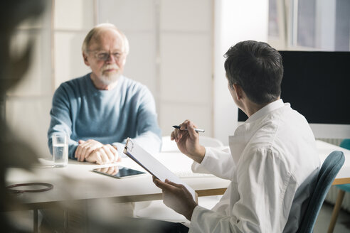 Doctor talking to senior patient in medical practice - JOSF02775
