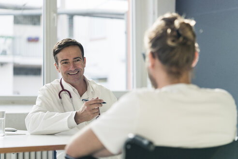 Smiling doctor talking to patient in wheelchair in medical practice - JOSF02778