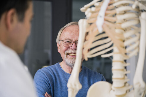 Smiling senior patient with doctor in medical practice with anatomic model - JOSF02781