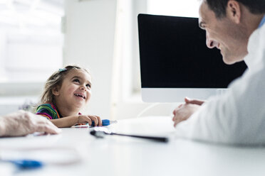 Doctor and smiling girl at desk in medical practice - JOSF02796