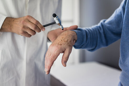 Close-up of doctor examining senior patient in medical practice - JOSF02814