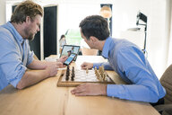 Two men playing chess and checking smartphone - JOSF02826