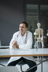 Doctor sitting at desk in medical practice with skeleton in background - JOSF02835