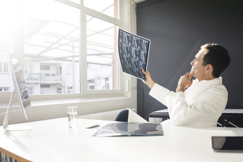 Doctor examining MRT image at desk in medical practice - JOSF02838