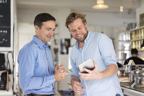Two smiling businessmen sharing tablet - JOSF02847