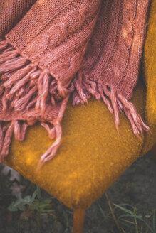 Blanket on orange chair outdoors - ASCF00911