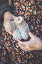 Close-up of pregnant woman holding baby shoes - ASCF00914