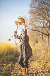 Happy pregnant woman standing on forest path playing with autumn leaves - ASCF00923