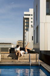 Couple relaxing on rooftop terrace at the pool - VABF02118