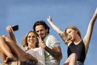 Friends having fun on a rooftop terrace, taking selfies - VABF02121