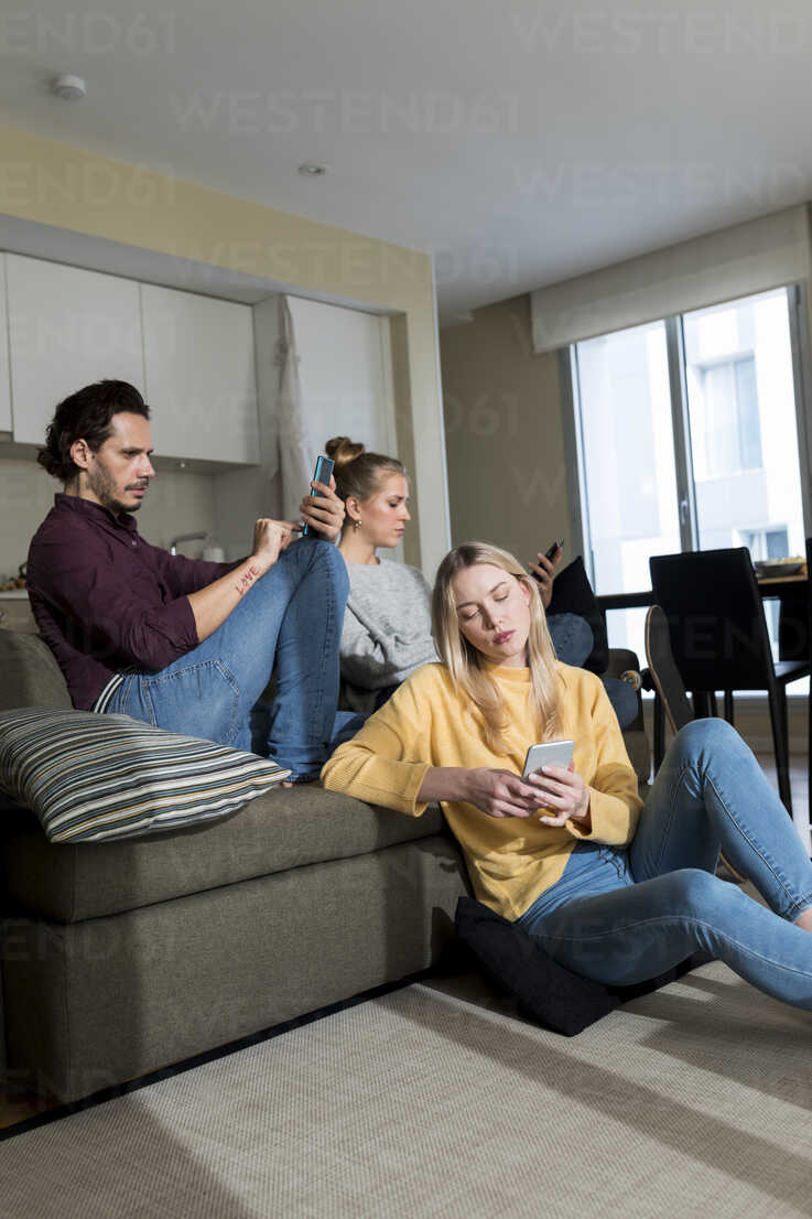 Bored friends sitting on couch in livingroom, using digital devices - VABF02181 - Valentina Barreto/Westend61