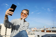 Young woman taking smartphone selfies on an urban rooftop terrace - VABF02199