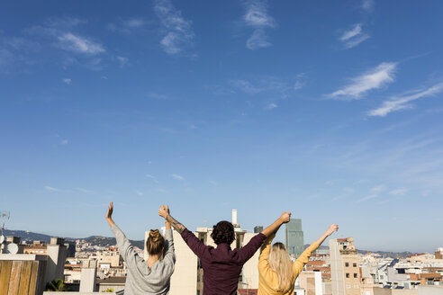 Spain Barcelona,  three friends back portrait  on a sunny day at a rooftop city view, urban friends group three young atractive happiness barcelona back - VABF02202