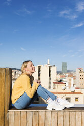 Young woman relaxing on an urban rooftop terrace - VABF02205
