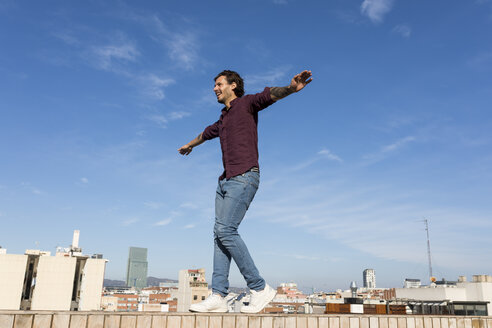 Man on a rooftop terrace, balancing on a wall - VABF02208