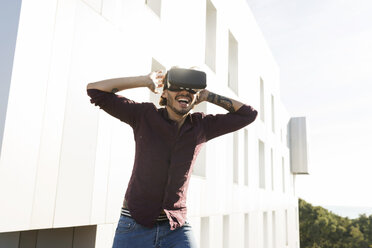 Man on a rooftop terrace, gaming with VR glasses - VABF02214