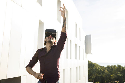 Man on a rooftop terrace, gaming with VR glasses - VABF02217