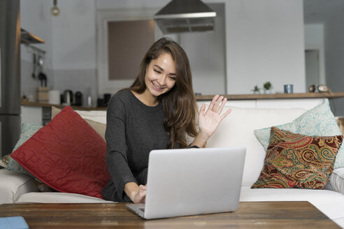 Young woman sitting on her couch, chatting on her laptop - ERRF00614