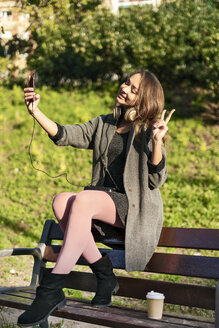 Young woman sitting on a park bench, taking smartphone selfies, making victory sign - ERRF00644