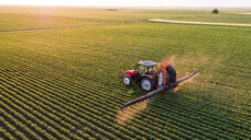 Serbia, Vojvodina, Aerial view of a tractor spraying soybean crops - NOF00074