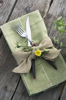 Burlap ribbon and herbs around napkin and silverware - HEROF04620