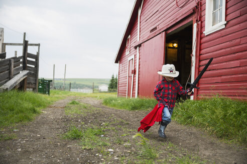 Boy with sword running outside barn - HEROF04653