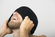 Laughing bearded man covering face with stocking-cap - HEROF04716