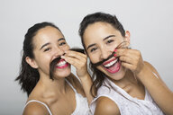 Portrait of brunette twin sisters with pretend mustaches - HEROF04734