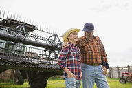 Grandfather and grandson in front of combine harvester - HEROF04776