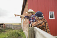 Grandfather and grandson leaning on fence on farm - HEROF04779