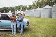 Farmers talking outside truck on farm - HEROF04782