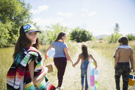 Family walking with beach equipment in rural sunny summer field - HEROF04800