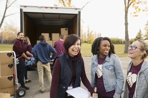 Female volunteers laughing outside truck - HEROF04935