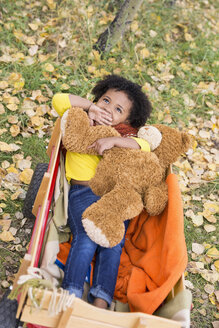 Girl laying in wagon with teddy bear in autumn leaves - HEROF04938