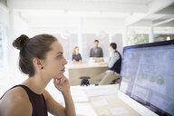 Female architect drafting digital blueprint at laptop in open plan office - HEROF04977