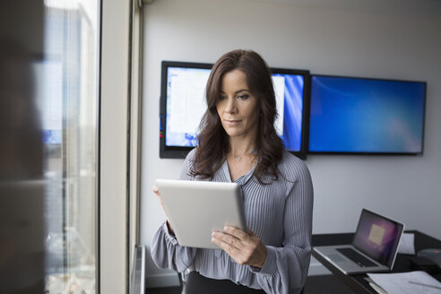 Businesswoman using digital tablet in conference room - HEROF05007