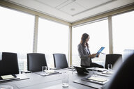 Businesswoman preparing for meeting using digital tablet in conference room - HEROF05031