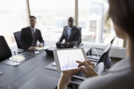 Businesswoman viewing bar chart on digital tablet in conference room meeting - HEROF05034