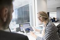 Businesswoman showing pie chart on digital tablet to businessman at urban office window - HEROF05037