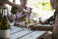 Couples wine tasting and enjoying charcuterie board on patio at winery tasting room - HEROF05094