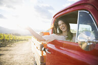 Carefree woman laughing riding in truck in sunny vineyard - HEROF05100
