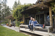 Couple relaxing drinking coffee on patio bench - HEROF05109