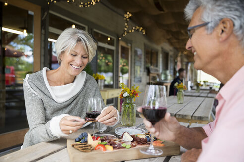 Couple enjoying wine and charcuterie at winery patio table - HEROF05124