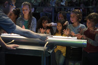 Children and scientist creating acoustic waves using a Rubens tube in science center theater - HEROF05181