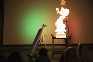 Children watching scientist creating fire in demonstration in science center theater - HEROF05184
